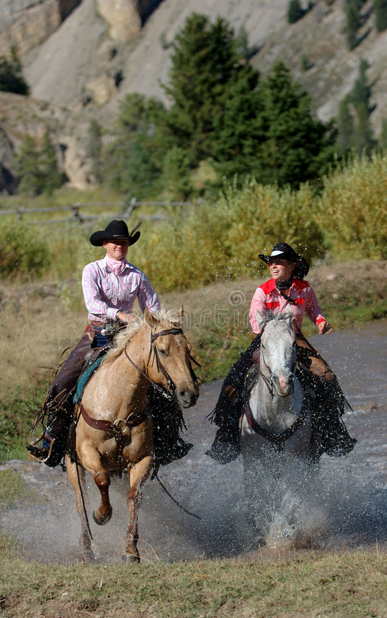 Two Cowgirls Emerging from Pond stock images