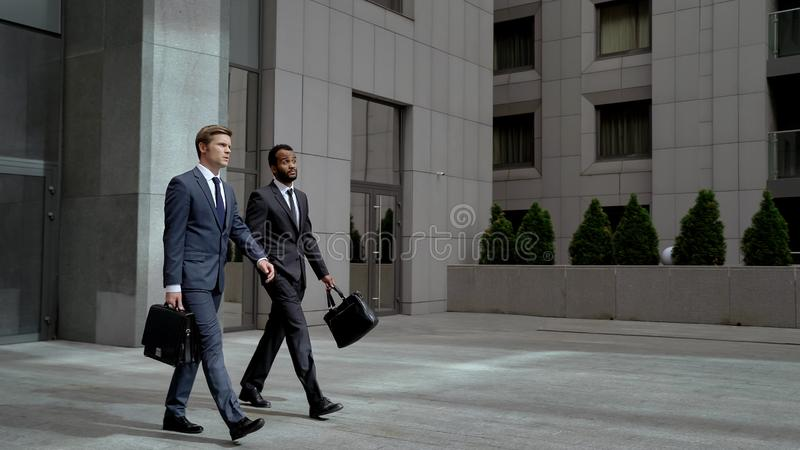 Two coworkers leaving business center after meeting with partners, business. Stock photo royalty free stock photo
