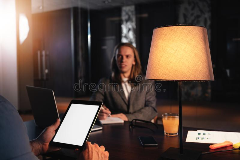 Two coworkers meet in night loft office. Manager conducts an interview. Dialogue of businessmen about a new startup stock photography