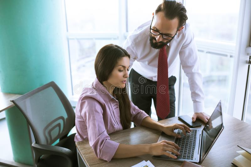 Business people planning strategy analysis. Two coworkers in offfice planning project milestone. Woman typing e-mail. Office concept royalty free stock photography