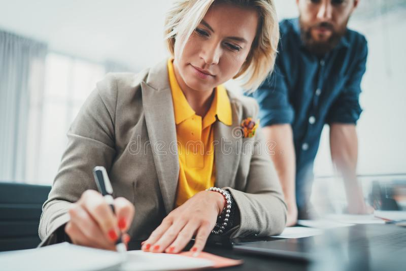 Two coworkers at working process.Young woman working together with colleague at modern office.Teamwork concept. royalty free stock photos