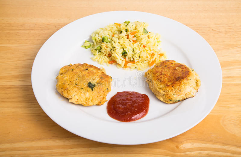 Two Crab Cakes with Cheesy Broccoli Rice stock images