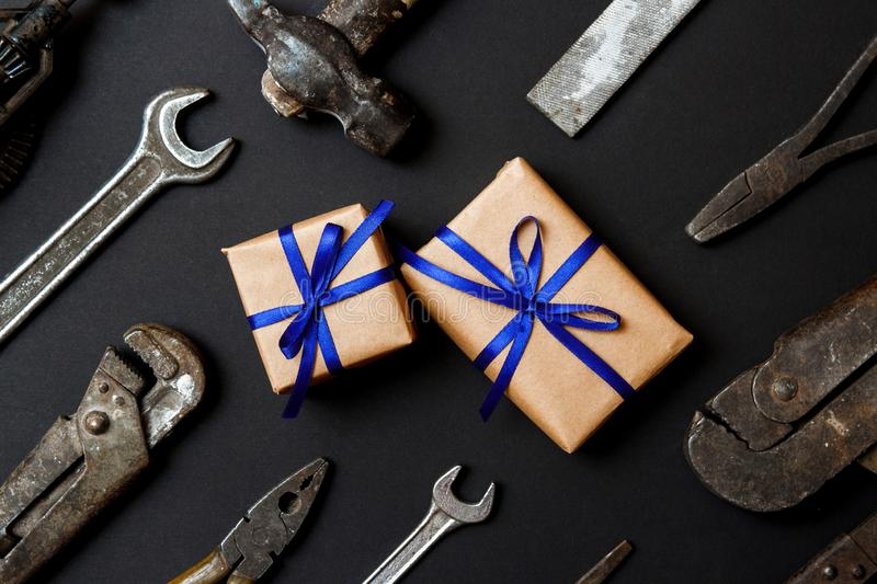 Two craft gifts with vintage old tools on black paper background. Fathers day concept. Flat lay.  royalty free stock photo