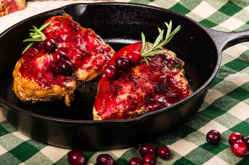 Two cranberry glazed chicken breasts in skillet. Two cranberry glazed chicken breasts in a cast iron skillet with berries stock photo