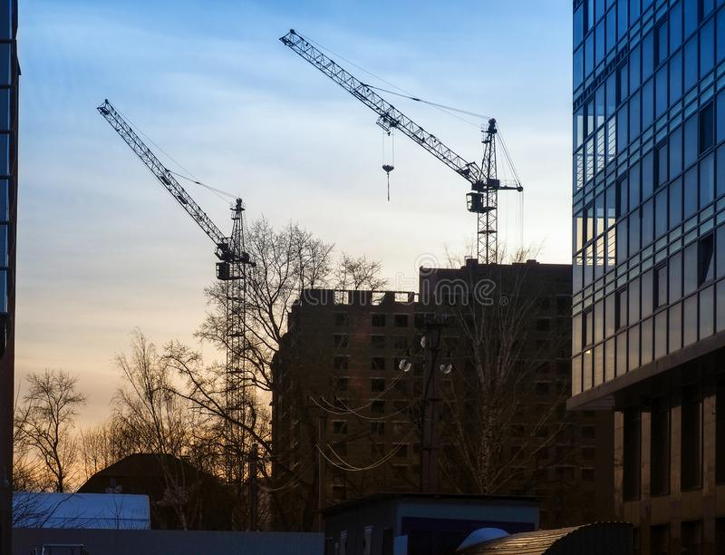 Two cranes raised their arrows over the unfinished multi-story building royalty free stock image