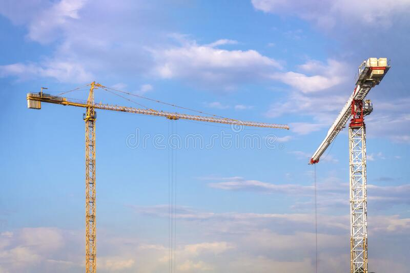 2 two cranes, yellow and white, against cloudy blue sky on sunny summer day.  royalty free stock photography
