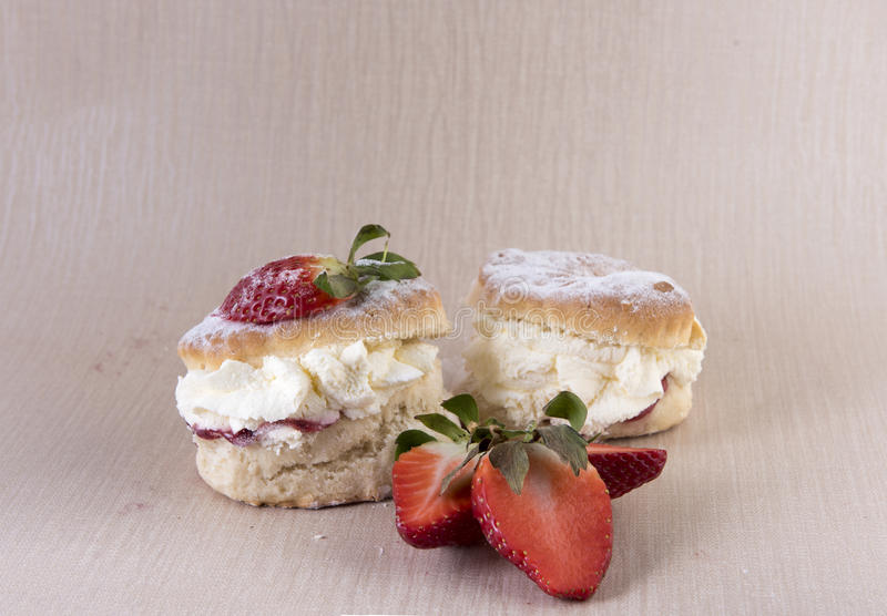 Two cream and strawberry jam scones. With sliced strawberries royalty free stock images