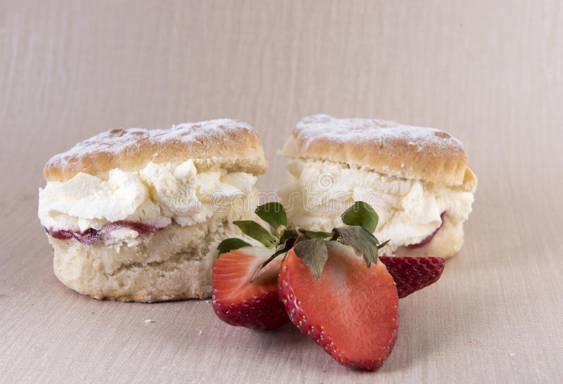 Two cream and strawberry jam scones. With sliced strawberries stock image