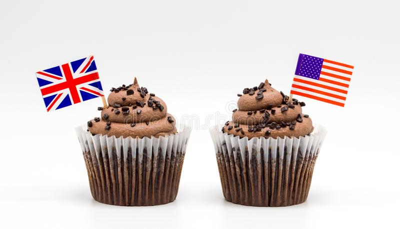 Two chocolate chip swirl cupcakes with tricolor American flag and British Union Jack flag toothpicks in them isolated on white stock image