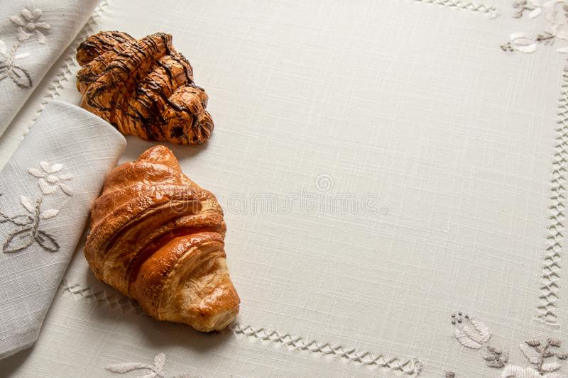 Two croissants with almonds, chocolate and powdered sugar on a table with napkins and tablecloth, closeup. Two freshly baked croissants with almonds, chocolate stock photos