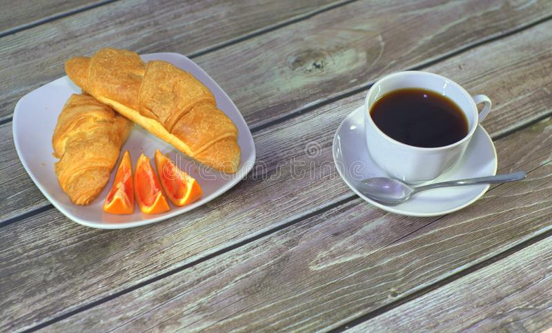Two croissants with orange slices on a plate and a cup of black coffee on a saucer with a spoon on the table. Close-up. Two croissants with orange slices on a stock photography
