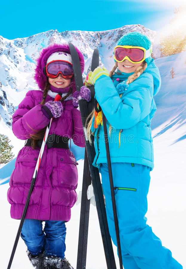 Two crosscountry girls. Two girls with crosscountry ski standing together with mountains on background royalty free stock photography