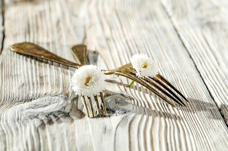 Two crossed forks with small white flowers on vintage wooden board background. Some empty space for text or decoration royalty free stock photo