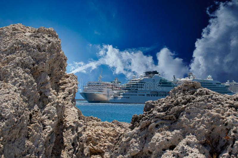 Two cruise liners between rocks foreground. Two cruise ships between foreground rocks with beautiful blue sky royalty free stock photography