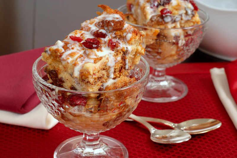 Two crystal goblets filled with Italian Panettone cranberry bread pudding with sauceboat in background stock photo