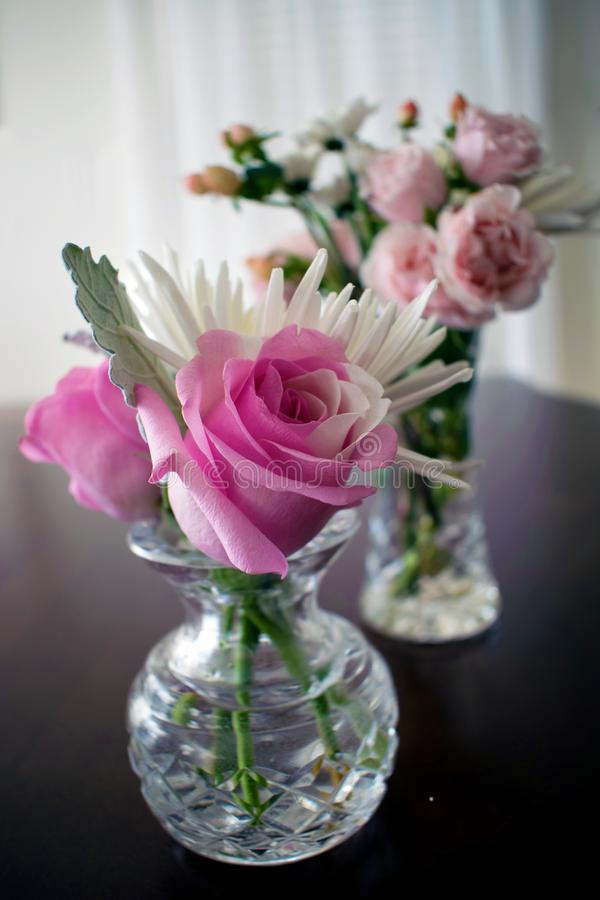 Two crystal vases filled with roses and other small flowers royalty free stock image