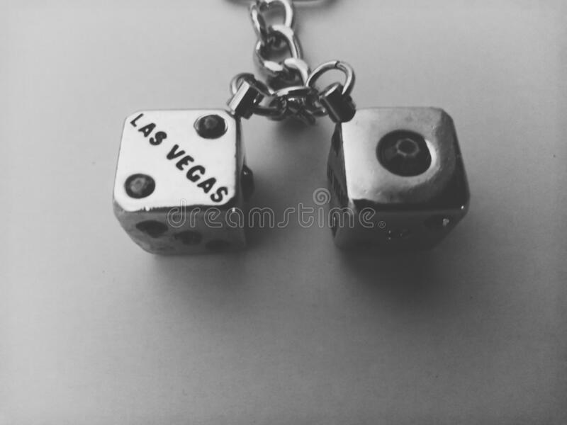 Two dices. Two cube  keyring dices in closeup in monochrome. On one dice appear the text & x22;Las Vegas& x22 stock images