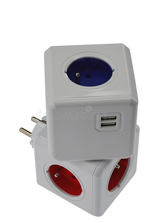 Two cube shaped multiplugs with USB ports for smart device charging placed at each other royalty free stock image