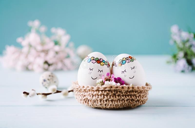 Two cuddling Eastereggs. With sweet faces lying in an easter basket, light blue background and free copyspace royalty free stock photography