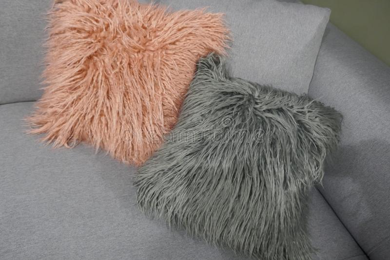 Two cuddly lambskin pillows on a gray sofa stock photo