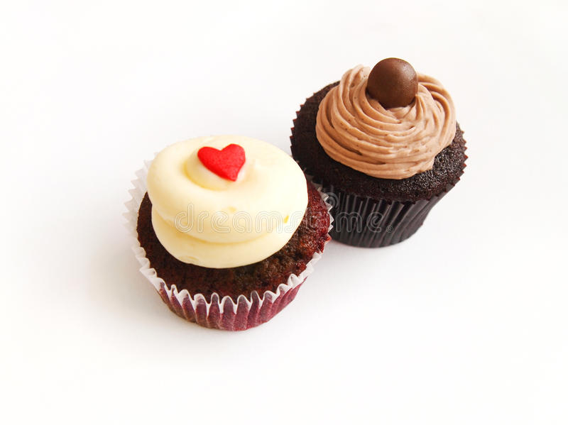 Two cup cakes. A photograph of 2 luxurious gourmet cupcakes in different flavors of red velvet with vanilla cream and chocolate cream. Delicious and pretty stock photo
