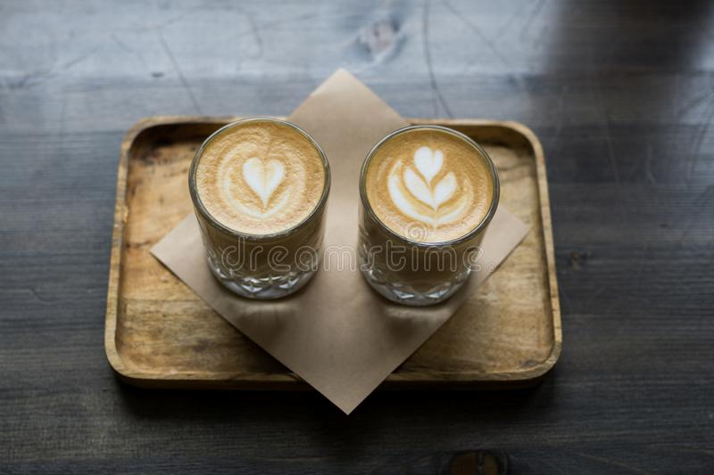 Two cup of cappuccino art on a wooden table. Bokeh background royalty free stock image