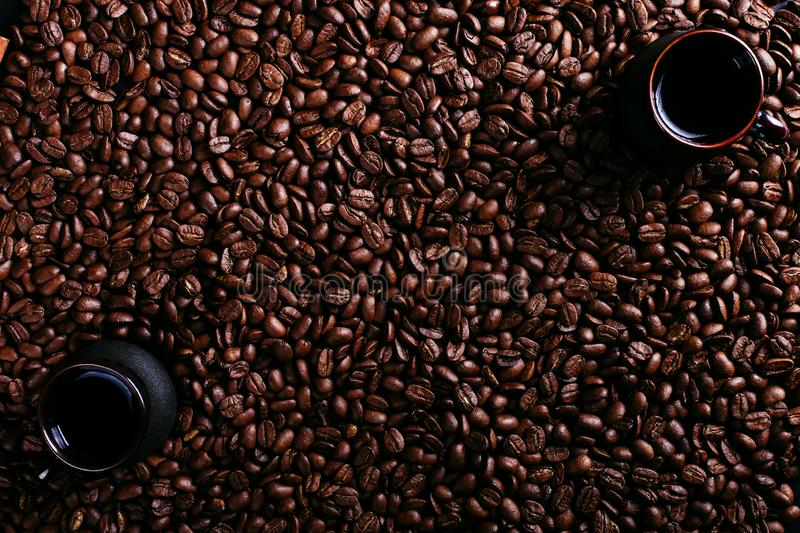 Two cup of coffee, star anise, cinnamon on the background of coffee beans. Fragrant spices for a drink, top view, flat ley stock photo