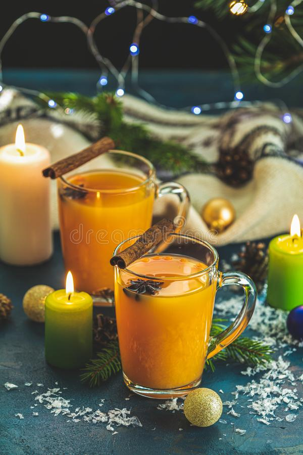 Two cup of hot spicy tea with sea buckthorn, cinnamon and star anise, branches of pine and spruce,  candles and holiday decor,. Christmas and New Year royalty free stock images