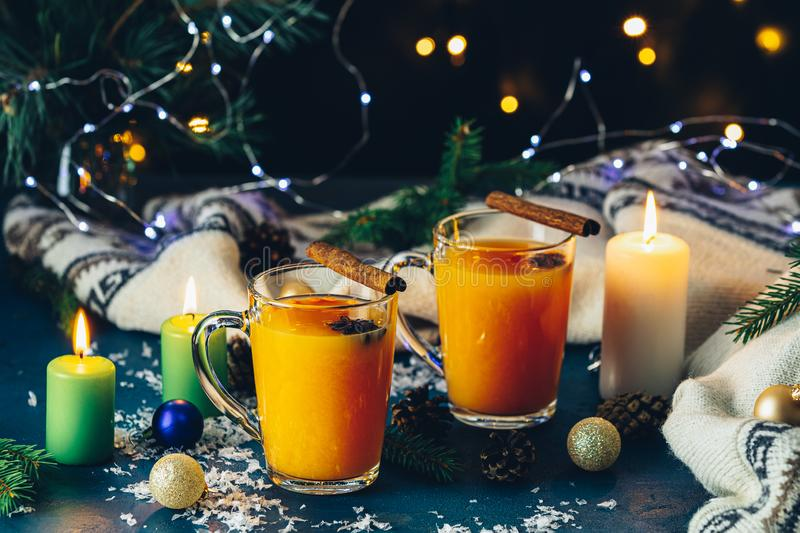 Two cup of hot spicy tea with sea buckthorn, cinnamon and star anise, branches of pine and spruce,  candles and holiday decor,. Christmas and New Year royalty free stock photo