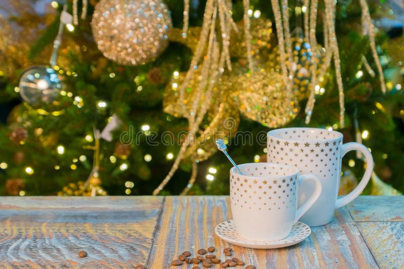 Two cup on rustic table with christmas decorated tree stock image