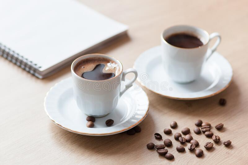 Two cup of turkish coffee close-up on a wooden background, coffee beans. Pleasant morning and cheerfulness. Two cup of turkish close-up on a wooden background royalty free stock photo