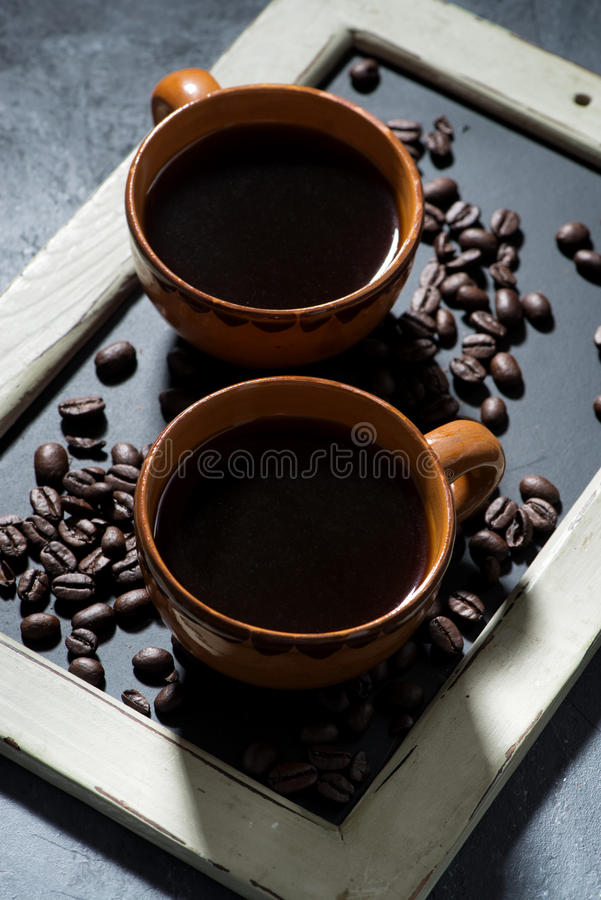 two cups of black coffee on the blackboard, top view vertical royalty free stock images