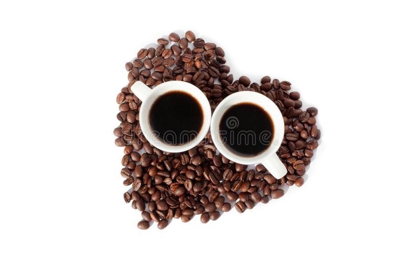 Two cups of black coffee and a heart made of coffee beans on white backgroung isolated top view royalty free stock photo