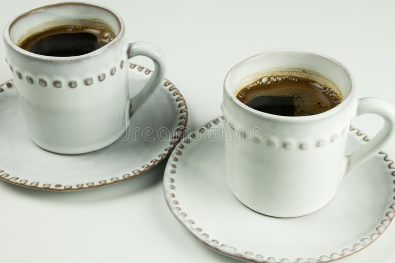 Two cups of black coffee and saucers on white background. royalty free stock photography