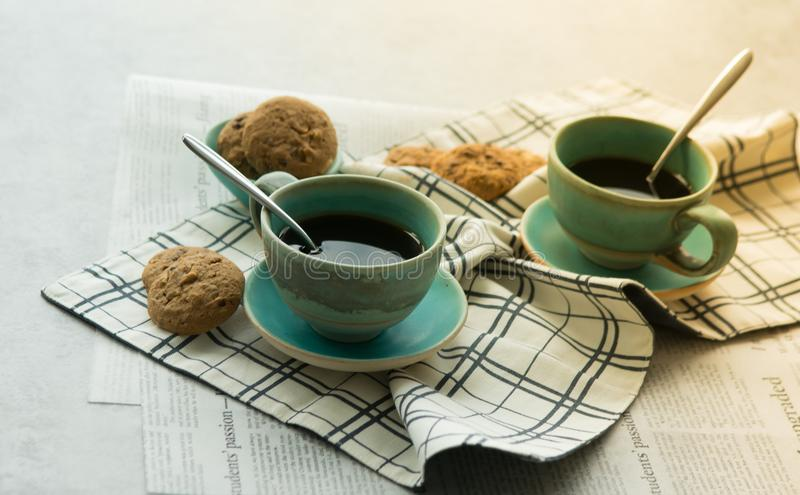 Two cups of black coffee with spoon on supported dish on fabric o royalty free stock photo