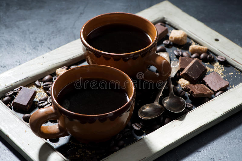 Two cups of black coffee, sugar and chocolate on a blackboard stock images