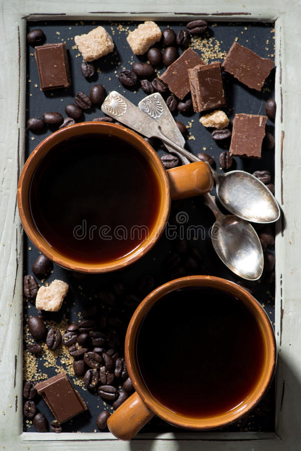 two cups of black coffee, sugar and chocolate on a blackboard stock photo