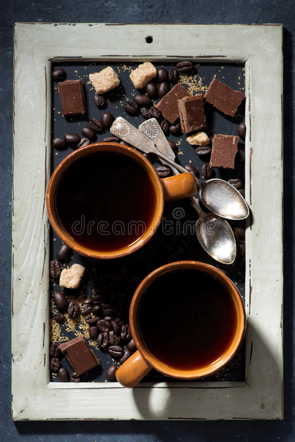 two cups of black coffee, sugar and chocolate on a blackboard royalty free stock photos