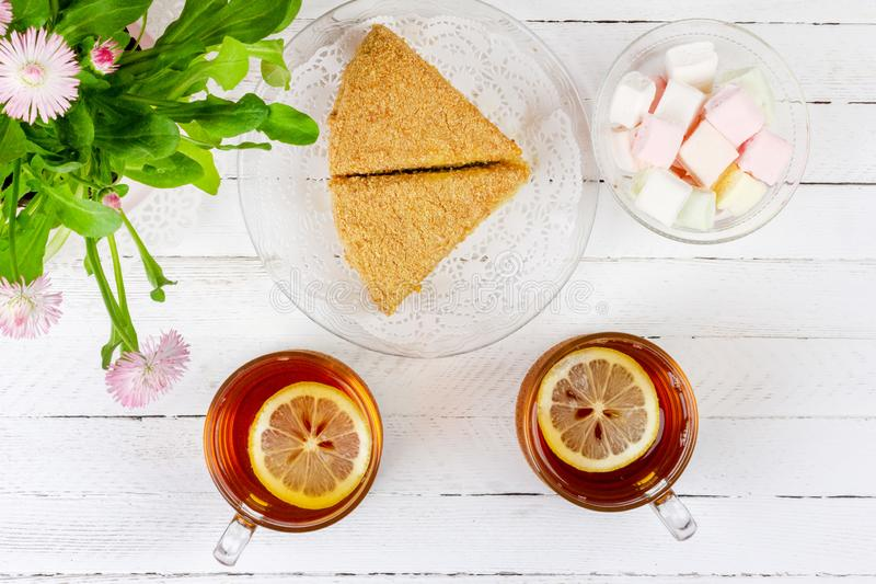 Two cups of black tea with lemon, pieces of cake, marshmallows and a pink flower on a white wooden table royalty free stock image