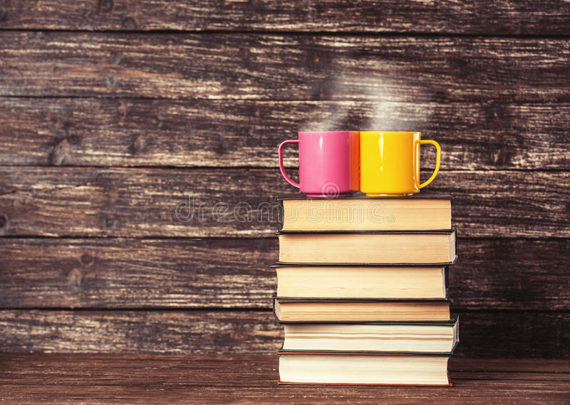 Two cups and books. Wooden table and background royalty free stock photography