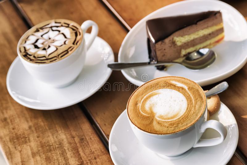 Two cups of Cappuccino coffee and chocolate mousse cake royalty free stock photos