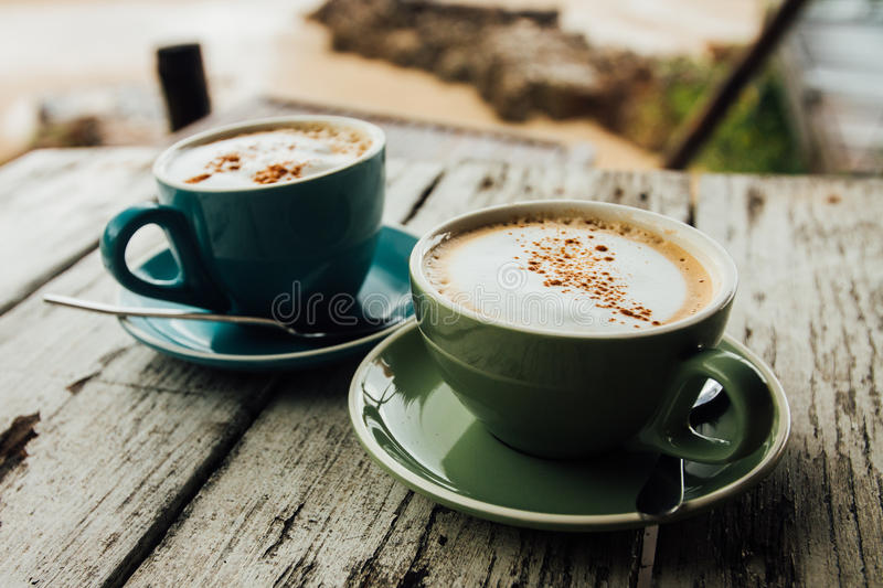 Download Two Cups Cappuccino Coffee Stand On Wooden Table. Green And Blue  Cup Coffee Stock