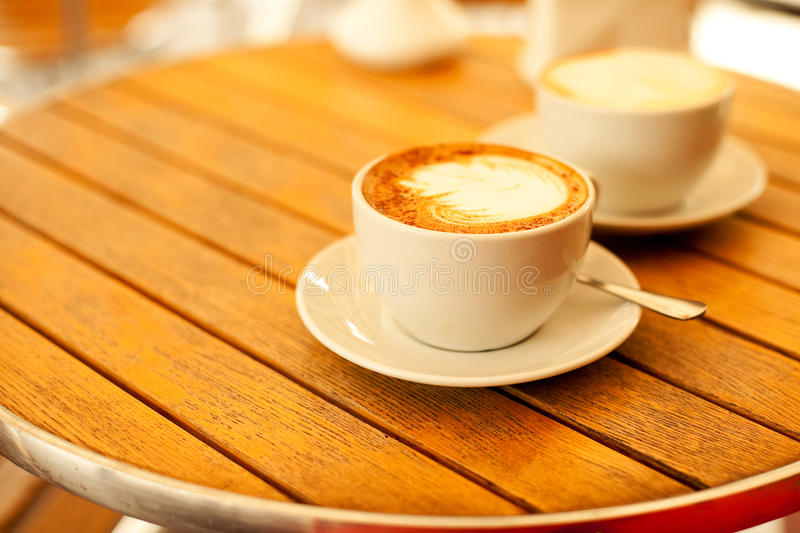 Two cups with cappuccino (hot coffee with milk) stock image