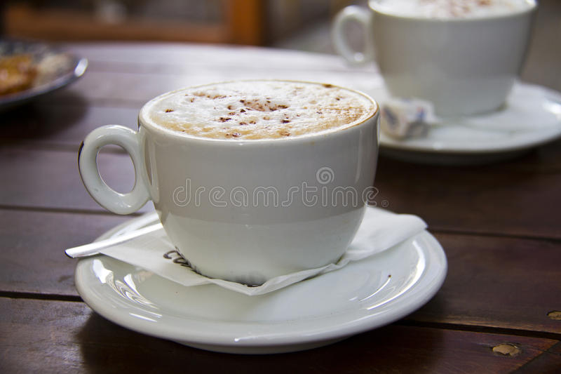 Two cups of cappuccino. Italian hot coffee drink - cappuccino served in cup in caffee royalty free stock image