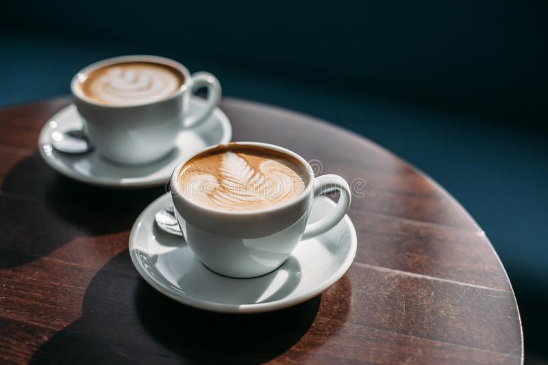 Two cups of cappuccino with latte art on wooden table. Beautiful foam, white ceramic cups stock image