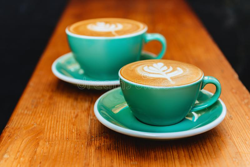 Two cups of cappuccino on wooden background. royalty free stock images