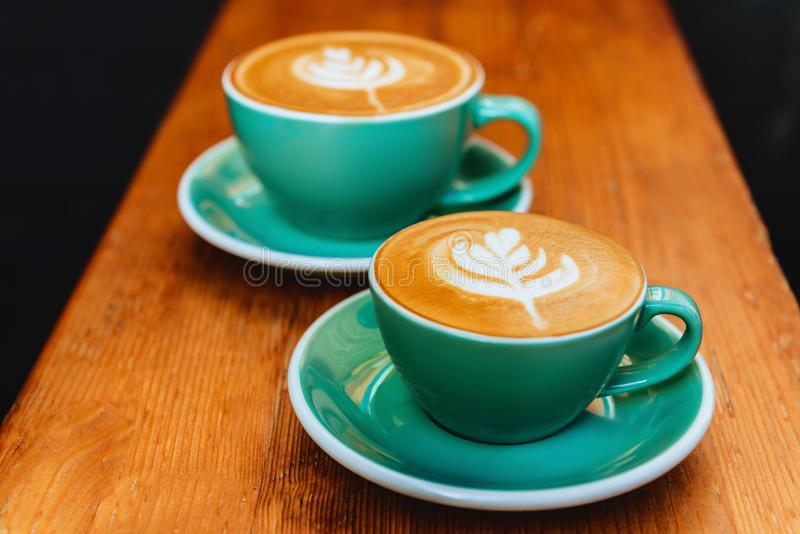 Two cups of cappuccino on wooden background. stock photos