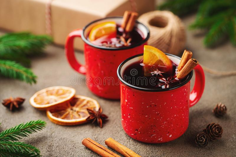 Two cups of christmas mulled wine or gluhwein with spices and orange slices on rustic table top view. Traditional drink on winter. Holiday stock photos