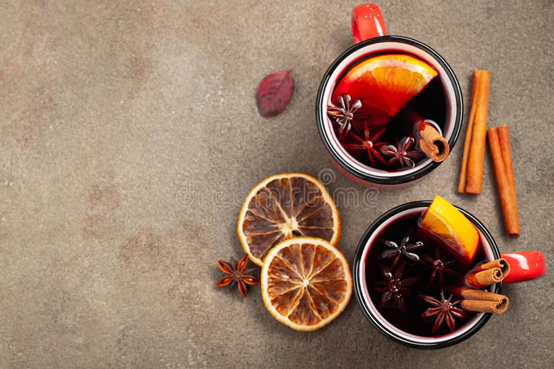 Two cups of christmas mulled wine or gluhwein with spices and orange slices on rustic table top view. Traditional drink on winter stock photo