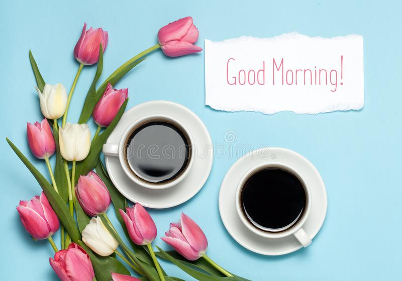 Two Cups of coffe and pink tulips on blue background. Words Good morning. spring coffee concept. top view, flat lay royalty free stock image